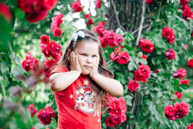 Крупным планом портрет хмурящейся взволнованной девушки в красной футболке, держащей щеки под аркой с ...