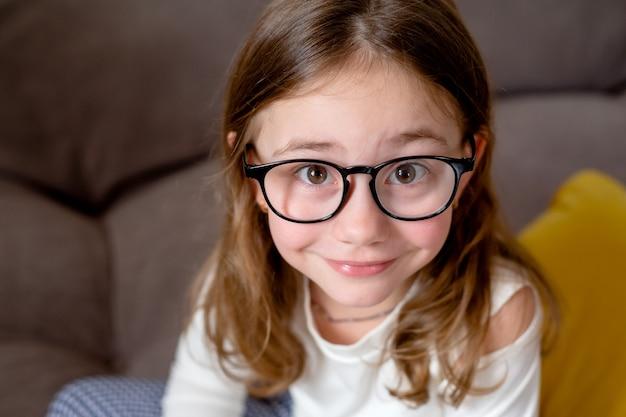白いプルオーバーで黒い縁のメガネと面白いかわいい女の子のクローズアップの肖像画