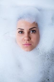 Портрет крупного плана девушки в ванне и белой пене вокруг ее лица. разные эмоции, гримасы, женская улыбка