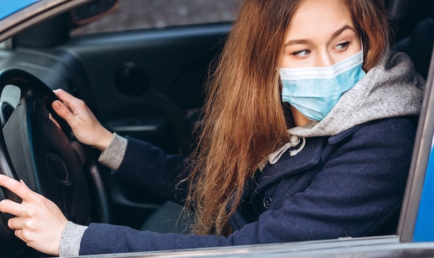 Портрет крупного плана девушки в медицинской маске в автомобиле. коронавирус эпидемия. движение по городу в условиях пандемии. женщина нарушила правила самоизоляции. sars-cov-2. стоп covid-19.
