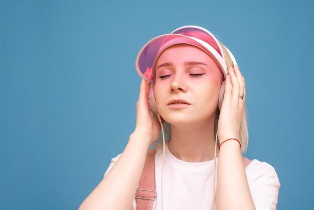 흰색 티셔츠와 분홍색 모자에있는 여자의 근접 촬영 초상화, 파란색에 닫힌 그녀의 눈을 가진 그녀의 헤드폰에서 음악을 듣는