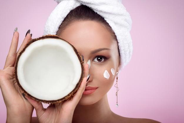 Крупным планом портрет девушки с полотенцем на голове и мазки натурального крема на щеке