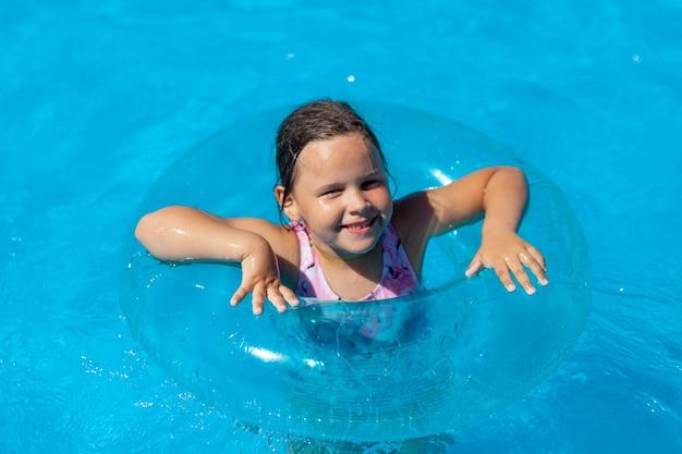 가족 휴가에 수영장의 푸른 맑은 물에서 수영하는 행복한 소녀의 근접 촬영 초상화...