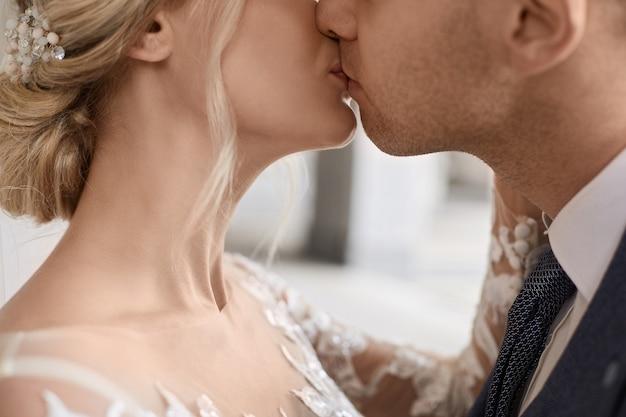 Портрет крупным планом великолепной невесты и модного жениха, целующихся во время свадебной церемонии.