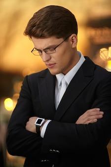 안경과 검은 양복을 입고 팔짱을 끼고 포즈를 취한 잘생긴 사업가의 초상화는 손에 시계를 차고 있습니다.