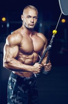 체육관에서 잘 생긴 남자의 클로 우즈 업 초상화입니다. 체육관에서 6 팩 근육질 가슴과 어깨를 가진 강력한 보디 빌더.