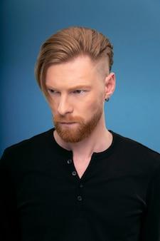 横を見て、ハンサムな赤毛のひげを生やした男のクローズアップの肖像画