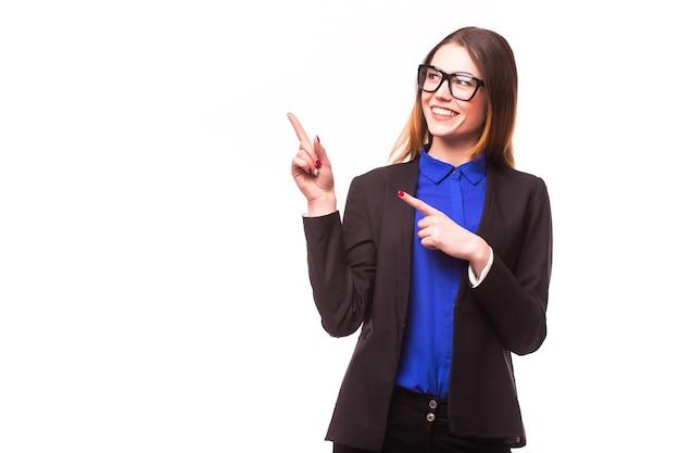 Крупным планом портрет счастливой молодой деловой женщины, указывающей на что-то интересное у белой стены
