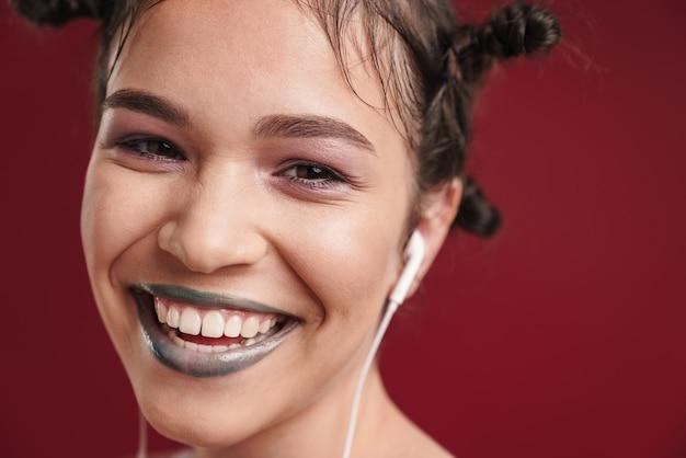 ブルゴーニュの赤い壁に分離されたイヤホンで音楽を聴いて幸せな若いパンク10代の少女のクローズアップの肖像画