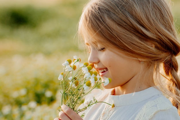 Крупным планом портрет маленькой девочки нюхает ромашки