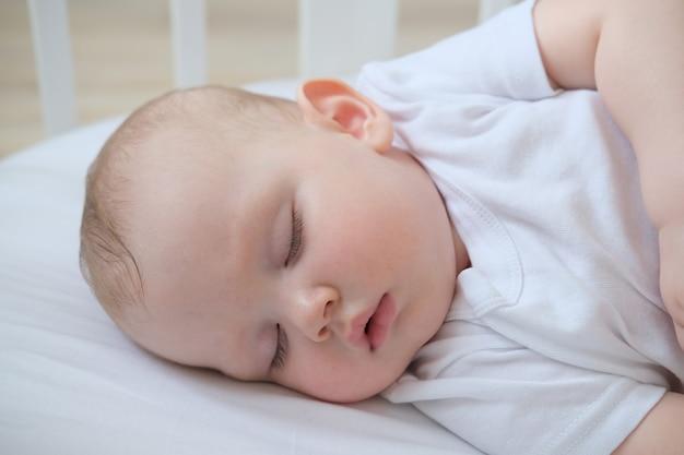 Крупным планом портрет маленького спящего ребенка в кроватке