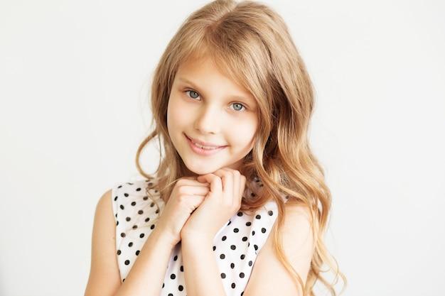 白い背景の上の素敵な少女のクローズアップの肖像画