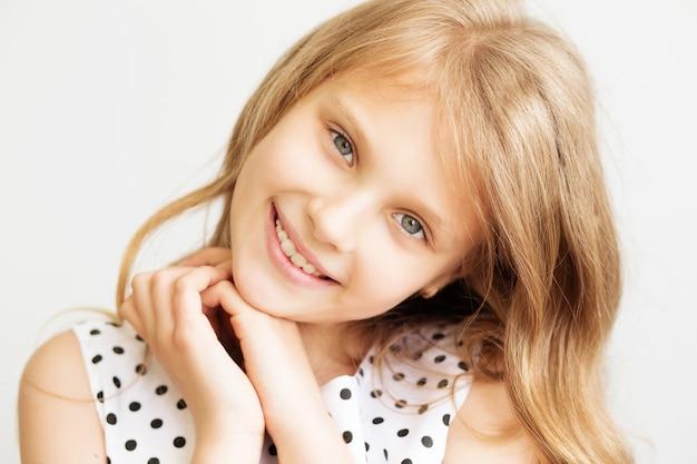 白い背景の前で素敵な笑顔の少女のクローズアップの肖像画