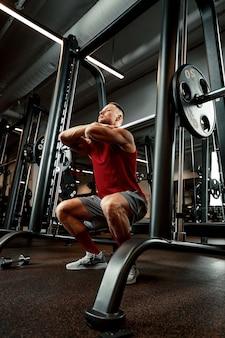 ジムでバーベルと筋肉の男のトレーニングのクローズアップの肖像画。 6パック、完璧な腹筋、肩、上腕二頭筋、上腕三頭筋、胸を持つ残忍なボディービルダーアスリート男。