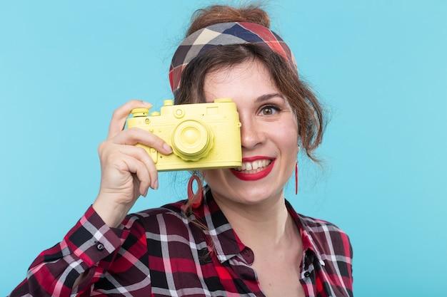 Портрет крупным планом позитивной красивой молодой женщины в клетчатой рубашке, фотографирующей с