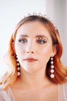 Портрет крупным планом рыжеволосой и косо одетой женщины с жемчужным макияжем, жемчужной повязкой на голове и ...