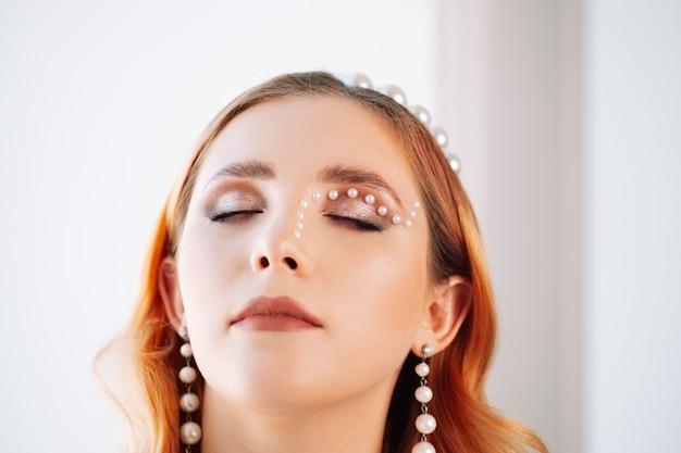 Крупным планом портрет рыжеволосой кавказской женщины с закрытыми глазами с жемчужным макияжем жемчужной матерью ...