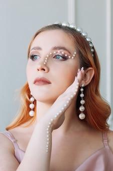 Крупным планом портрет рыжеволосой молодой женщины с макияжем из жемчуга в виде зигзага или ли ...