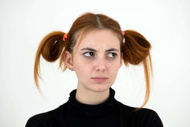 Портрет крупного плана грустной рыжей девочки-подростка с детской прической смотря обиженный изолированный на белом backround.