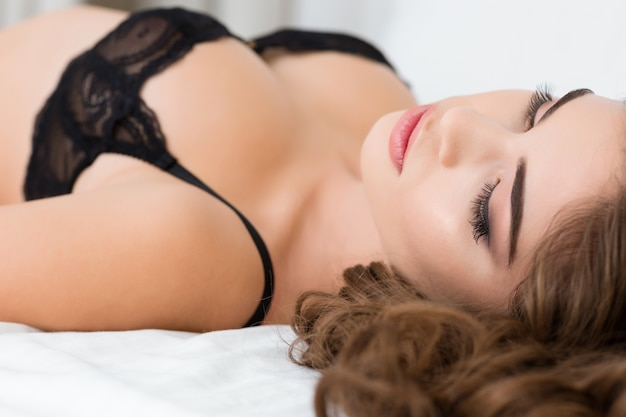 침대에 누워 란제리에 섹시한 여자의 근접 촬영 초상화