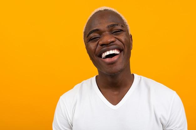コピースペースとオレンジ色の笑みを浮かべてハンサムな黒金髪アフリカ人のポートレート、クローズアップ