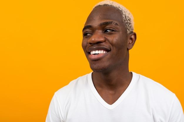 オレンジに笑みを浮かべてハンサムな黒金髪アフリカ人のポートレート、クローズアップ