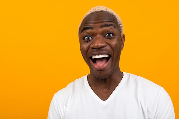 コピースペースとオレンジ色の顔をしかめると笑みを浮かべてハンサムな黒金髪アフリカ人のポートレート、クローズアップ