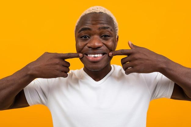 オレンジ色の顔をしかめると笑みを浮かべてハンサムな黒金髪アフリカ人のポートレート、クローズアップ