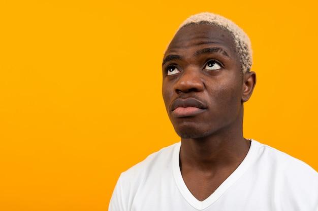 オレンジの思考の魅力的なハンサムな黒金髪アフリカ人のポートレート、クローズアップ