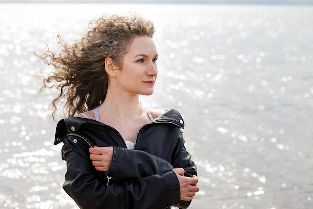 Портрет крупным планом кавказской женщины с вьющимися волосами в черной кожаной куртке смотрит в сторону на берегу воды