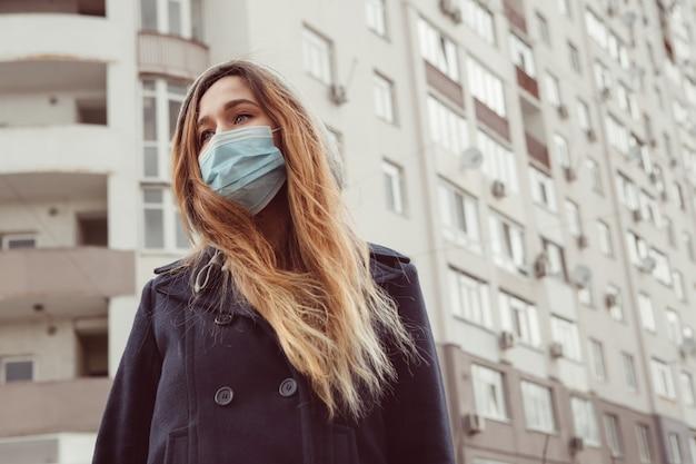 路上で医療用マスクを着た女性のポートレート、クローズアップ、コロナウイルスの流行。女性は自己分離のルールに違反しました。 sars-cov-2。 covid-19から身を守ってください。