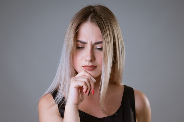 검은 tshirt에서 가벼운 벽 금발 여자에 찡그린 얼굴을 가진 여자의 근접 촬영 초상화