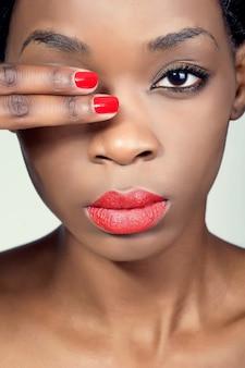 자연스러운 눈 화장과 붉은 입술을 가진 젊은 아프리카 여자의 근접 촬영 초상화