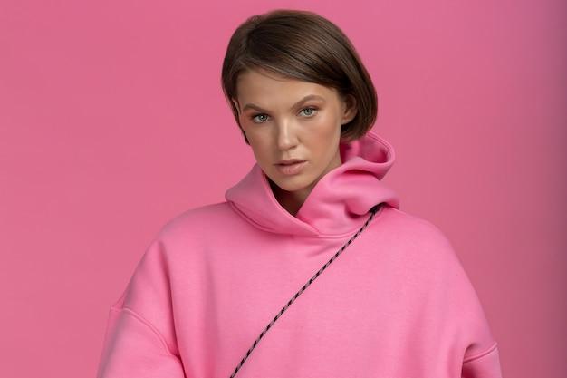 ピンクの背景にピンクのパーカーの若い美しいブルネットのクローズアップの肖像画