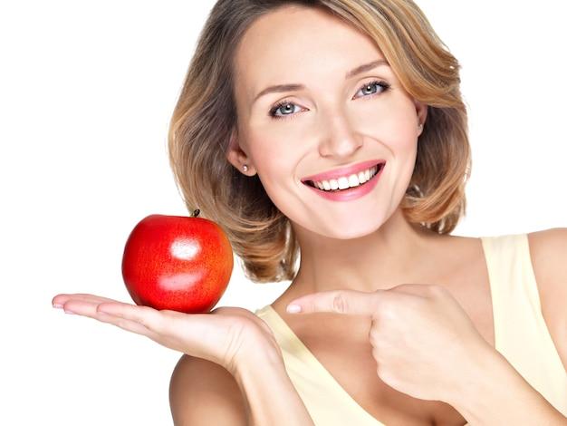 白で隔離のリンゴに指を指している若い美しい笑顔の女性のクローズアップの肖像画。
