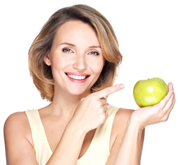 Крупным планом портрет молодой красивой улыбающейся женщины, указывая пальцем на яблоко - изолированное на белом.