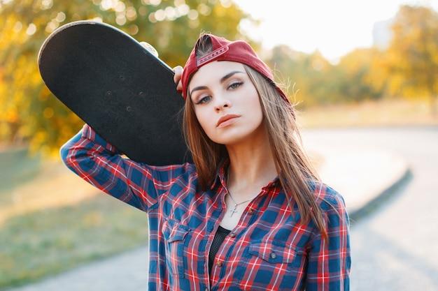 Крупным планом портрет молодой девушки в кепке, держащей скейтборд в парке на закате