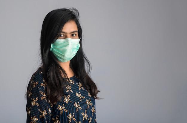 Макрофотография портрет молодой девушки или женщины, носящей медицинскую или хирургическую маску