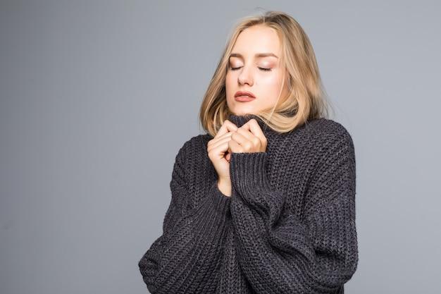 Крупным планом портрет молодой счастливой женщины в теплой зимней одежде на сером фоне