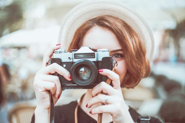 屋外のレトロなカメラで流行に敏感な若い女性のポートレート、クローズアップ
