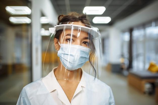 病院の廊下に立っている保護フェイスシールドと医療マスクを身に着けている若い看護師のクローズアップの肖像画。世界的なパンデミック発生時のコロナウイルスの予防。ヘルスケアの概念。