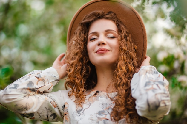 피 정원에서 봄 밝고 화창한 날을 즐기는 젊은 여자의 근접 촬영 초상화. 꽃 피는 나무 사이에서 흰 드레스와 갈색 모자를 쓰고 곱슬 갈색 머리를 가진 여성.