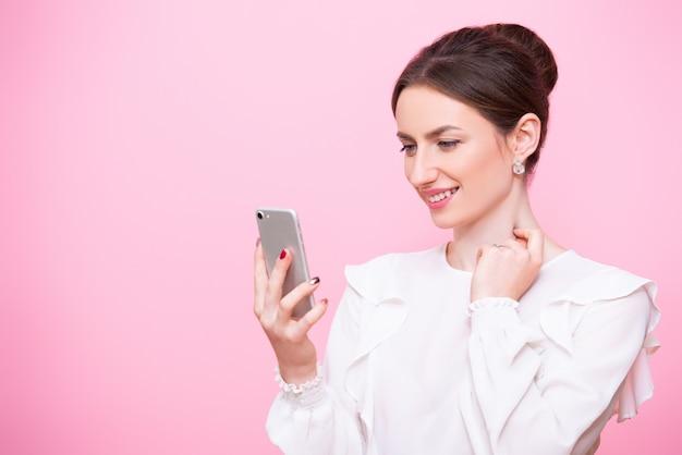 彼女の手で携帯電話とビジネススーツの若い女性のクローズアップの肖像画