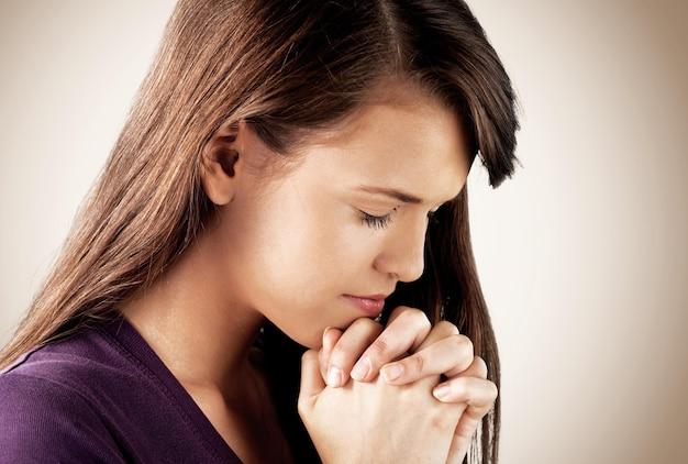 Крупным планом портрет молодой женщины молиться