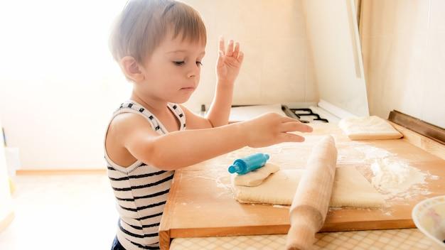 쿠키를 굽고 나무 rooling 핀으로 반죽을 압연 사랑스러운 3 세 유아 소년의 근접 촬영 초상화