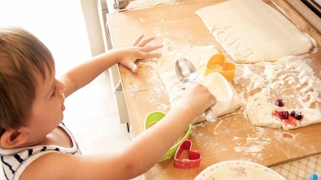 밀 반죽을 롤링 핀으로 돌리고 특수 플라스틱 커터로 쿠키를 자르는 사랑스러운 3세 소년의 클로즈업 초상화. 부엌에서 어린이 베이킹 및 요리