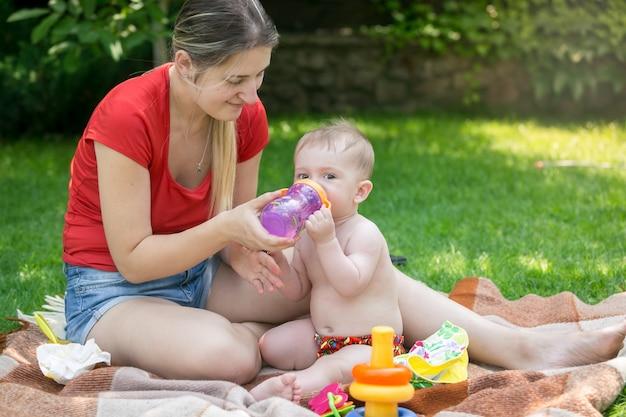 정원에서 피크닉에서 병에서 물을 마시는 사랑스러운 아기의 근접 촬영 초상화