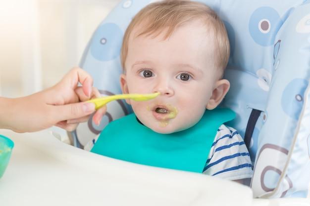 숟가락에서 과일 소스를 먹는 앞치마에 사랑스러운 아기의 근접 촬영 초상화
