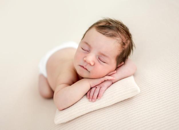 Портрет крупного плана очаровательной новорожденной девочки лежа на ее животике и спящей на крошечной подушке в студии. милый младенец ребенок дремлет, держась за руки под щеками