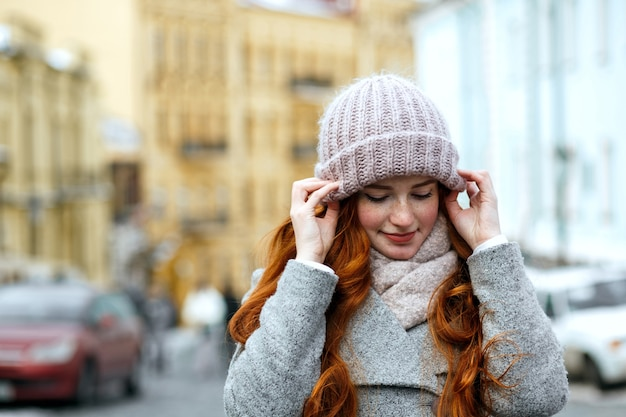 通りでポーズをとってニットの暖かい帽子とスカーフを身に着けている驚くべき赤い髪の女性のクローズアップの肖像画。テキスト用のスペース